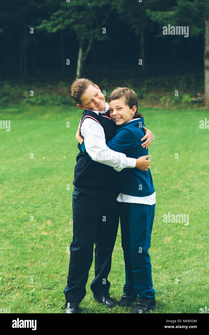 Two boys, brothers, schoolboys dressed up in formalwear hugging each other in front of a forest on a lawn in summer. - Stock Image