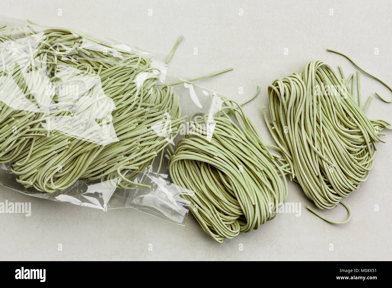 raw green tagliatelle in plastic bag - Stock Image