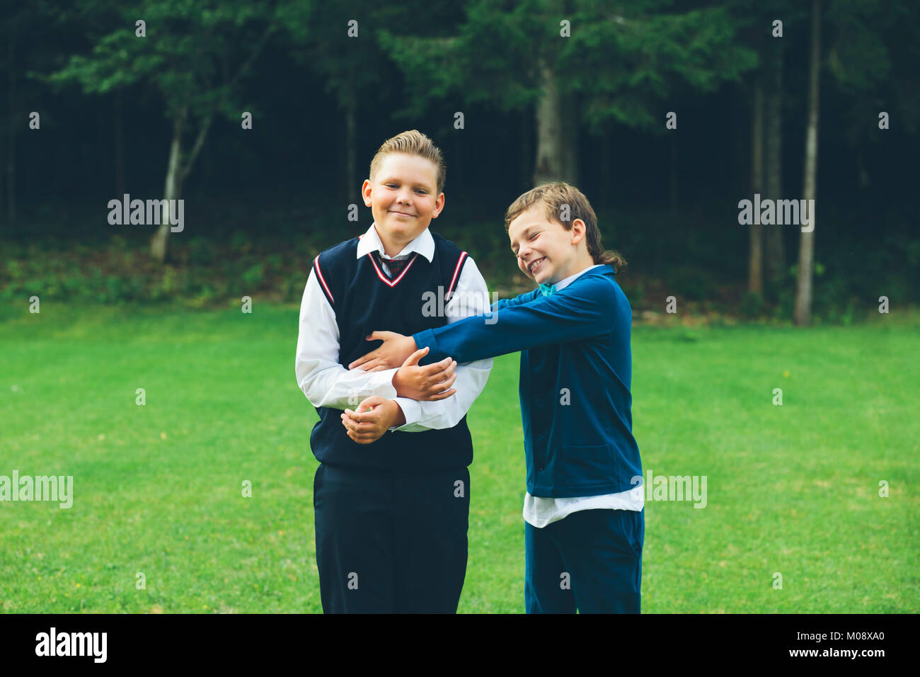 Two boys, brothers in formalwear are tugging each other, having fun in front of a forest on a lawn in summer. - Stock Image