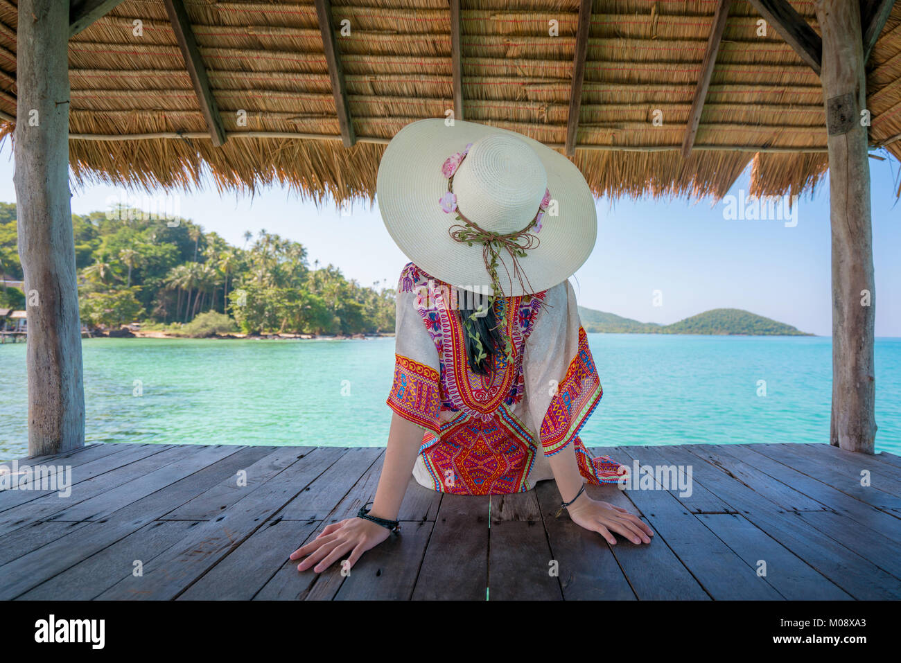 Beautiful Asian young woman relaxing in hut at tropical resort near the sea in Phuket, Thailand. Summer Vacation Stock Photo