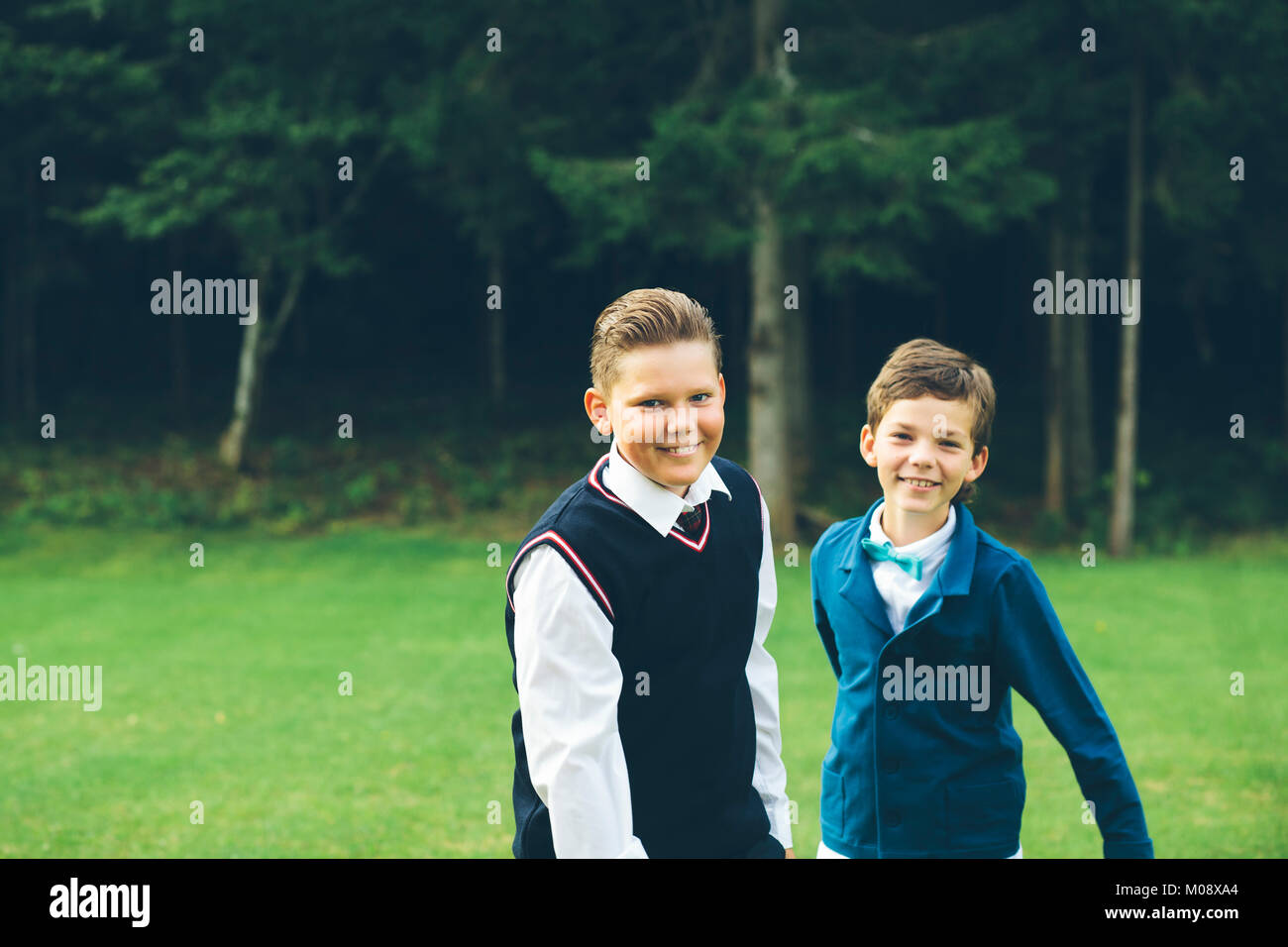Brothers try to pose for a portrait in their formalwear. - Stock Image