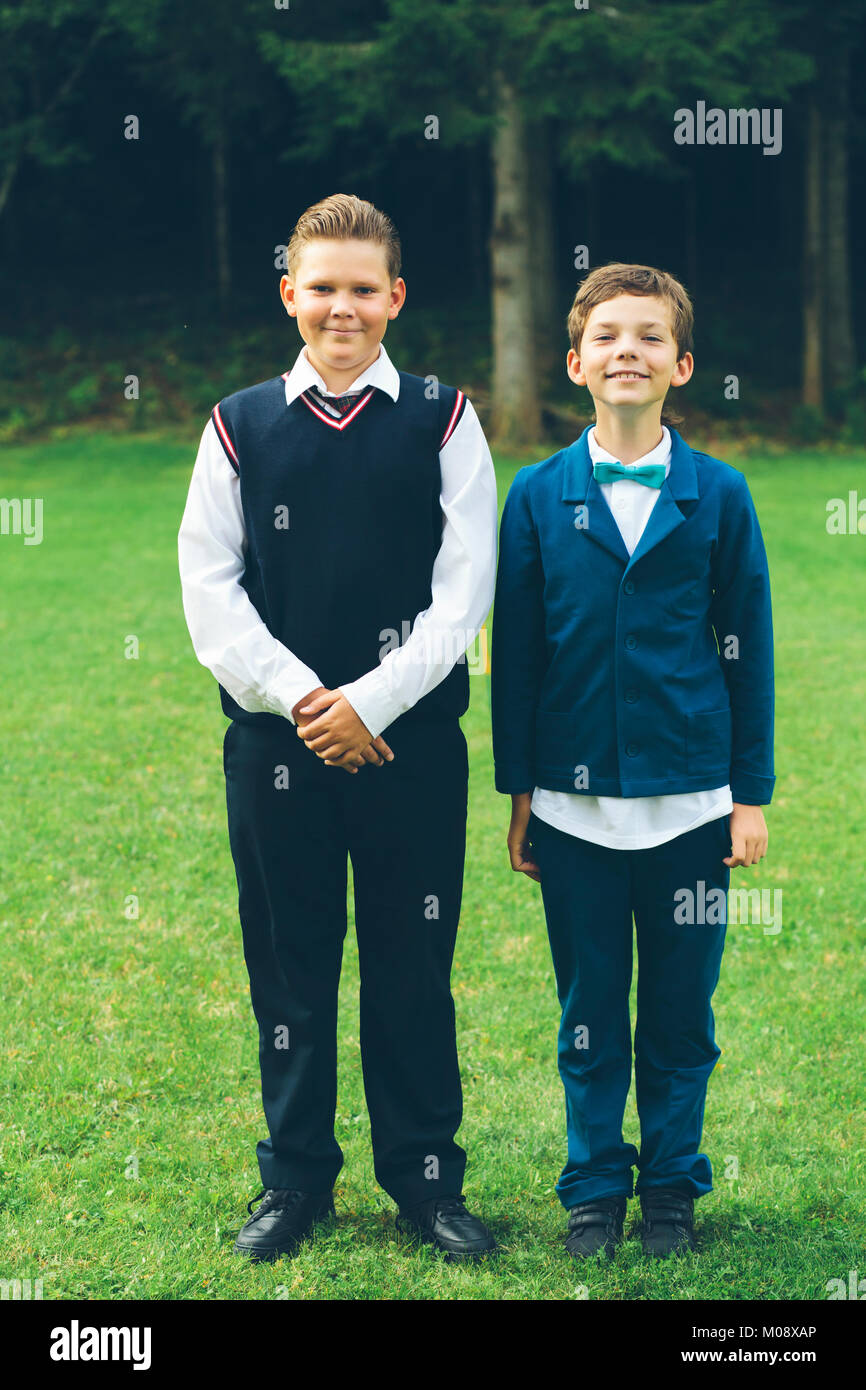 Formal portrait of two schoolboys standing next to forest. - Stock Image