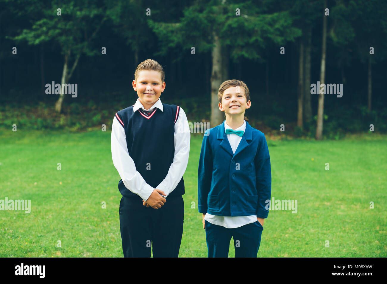 Two boys pose for a formal portrait in their backyard. - Stock Image