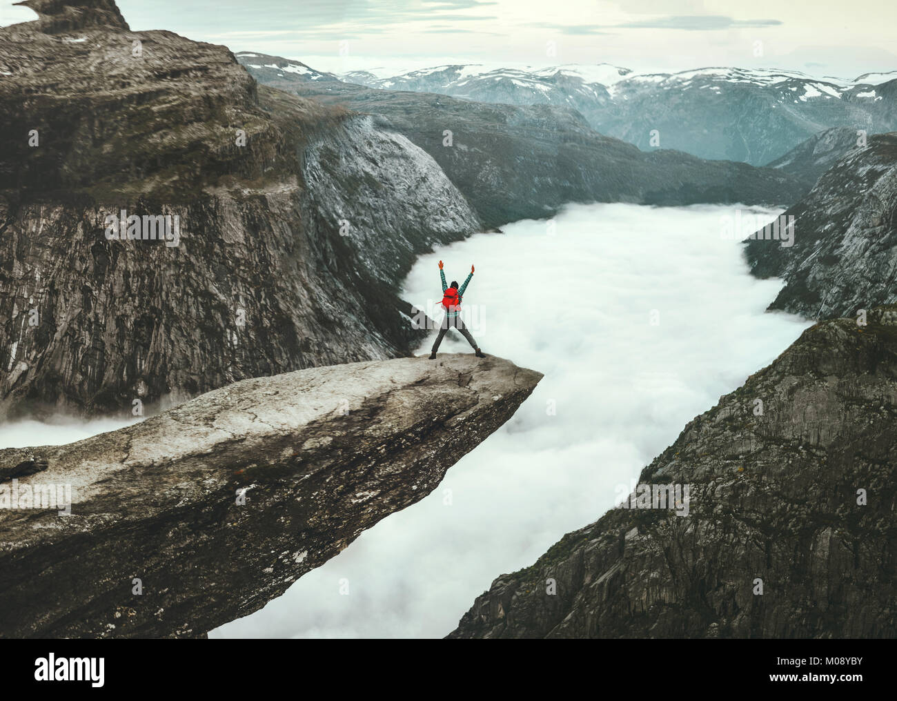 Man jumping on Trolltunga rocky cliff edge in Norway mountains Travel Lifestyle adventure happy emotional concept - Stock Image