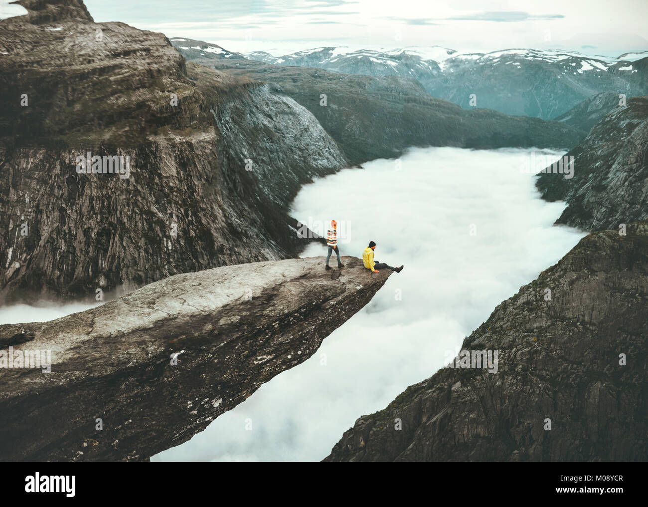 Couple Man and Woman on Trolltunga cliff in Norway above clouds Love and Travel emotions Lifestyle concept. Young - Stock Image