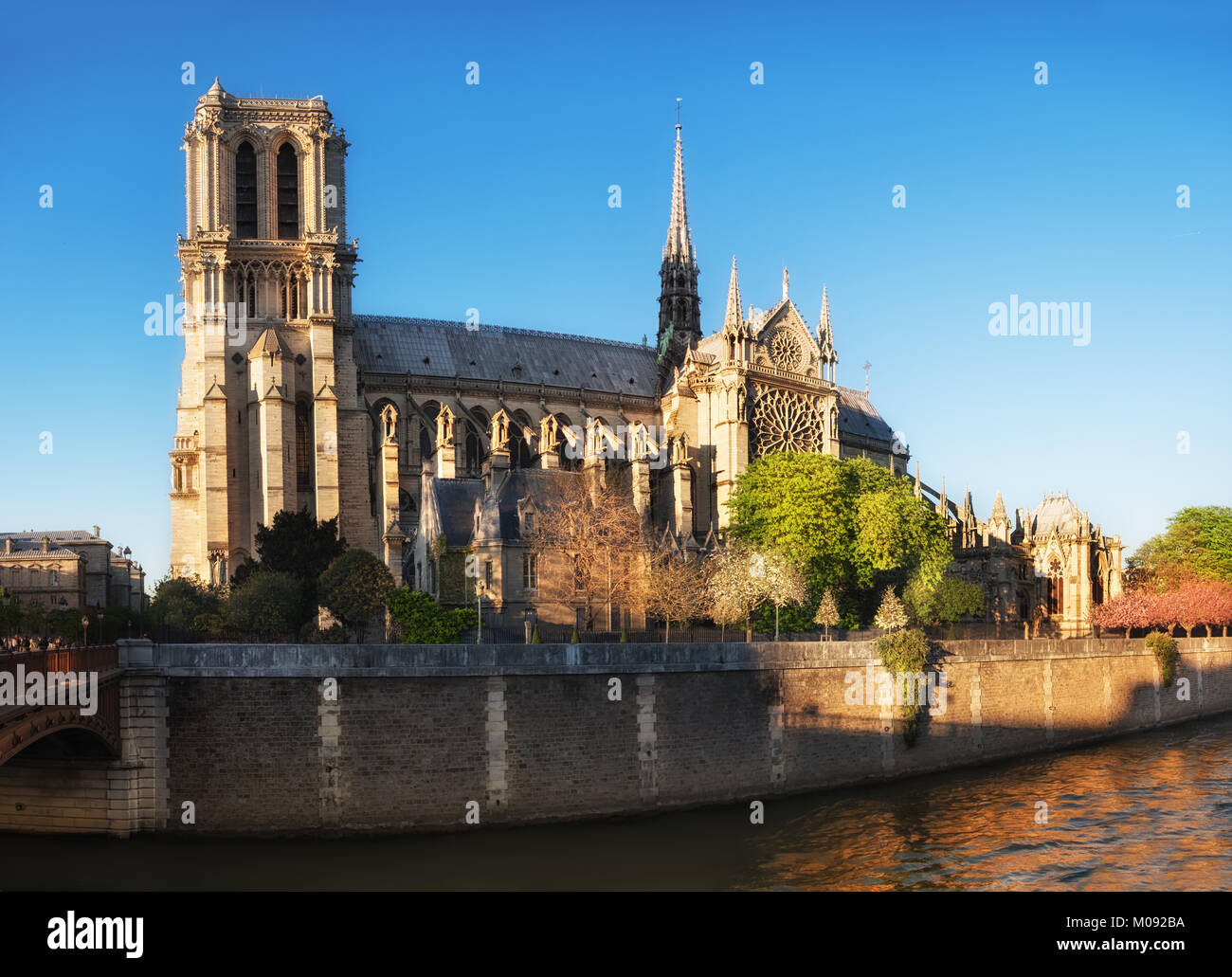 Notre Dame of Paris side view in Spring. Last rays of Sun in the evening. - Stock Image