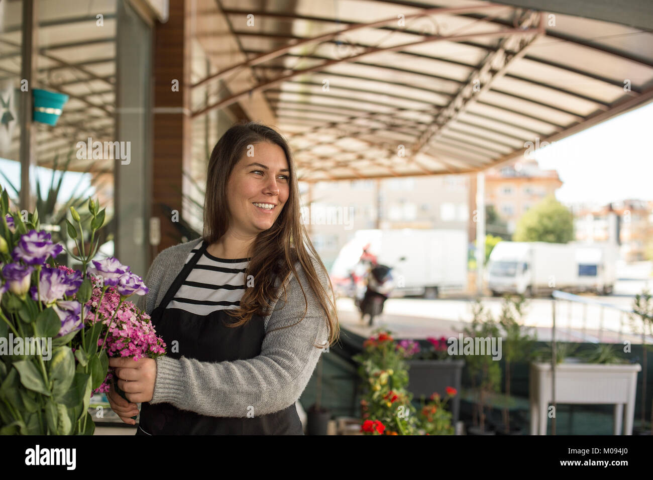 Small business concept. Smilng female florist picking flowers in a flower shop. - Stock Image