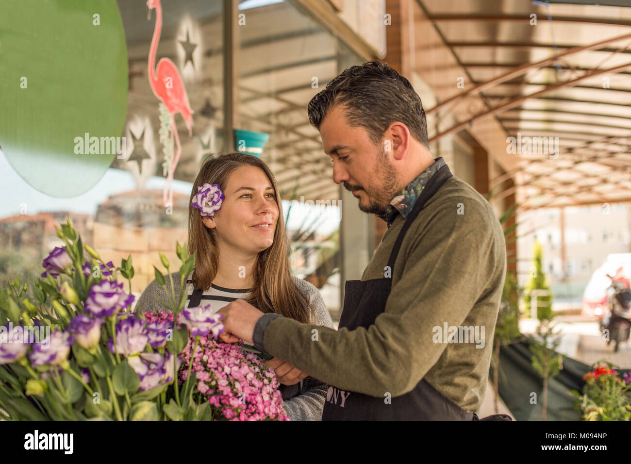 Small business concept. Male florist picking flowers and female florist with lisianthus in her hair looking at him - Stock Image