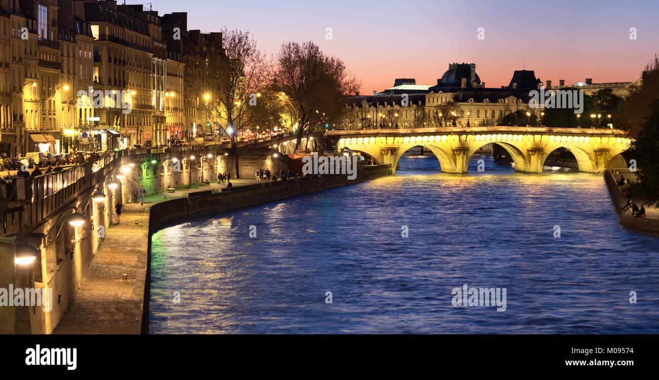 Evening Paris, panorama image along Seine river towards illuminated Pont Neuf on a sunset. - Stock Image