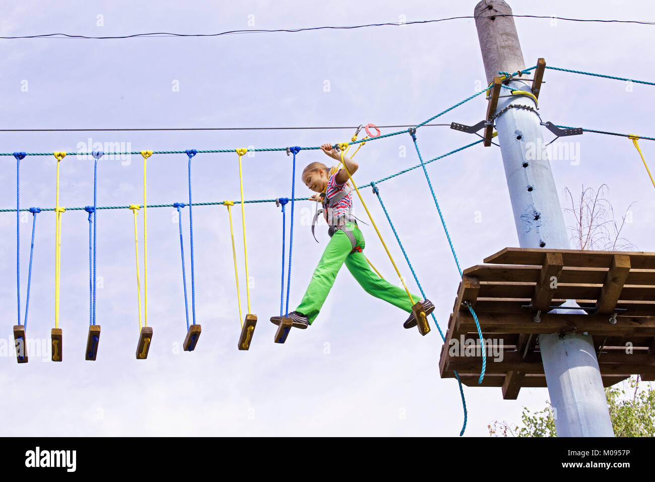 A teenage girl confidently moves on swinging boards at a height in a rope park. Courage and overcome - Stock Image