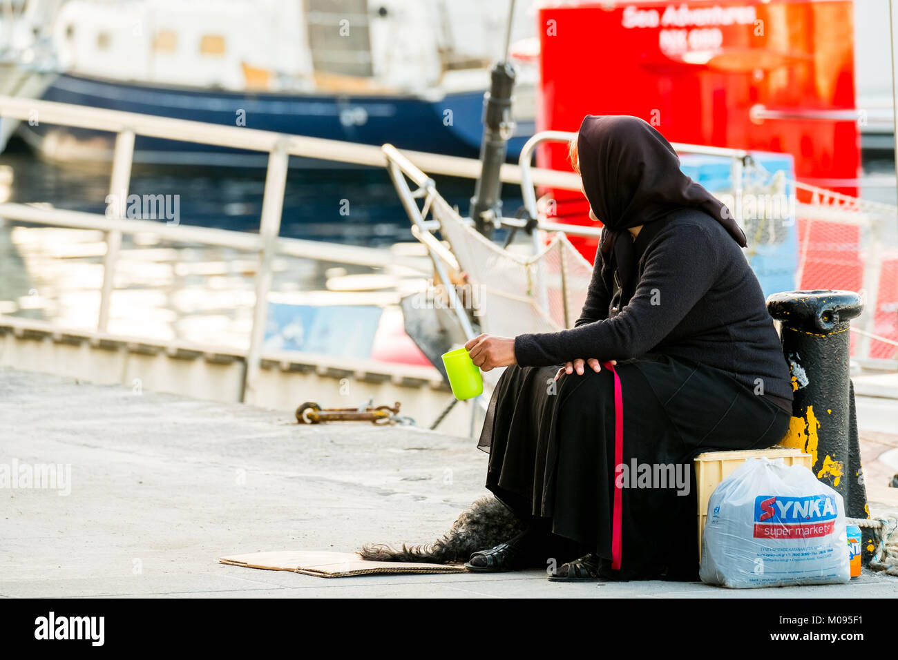 beggar woman in black robe in port of Chania, poverty, Europe, Crete, Greece, Chania, Europe, Crete, Greece, GR, Stock Photo