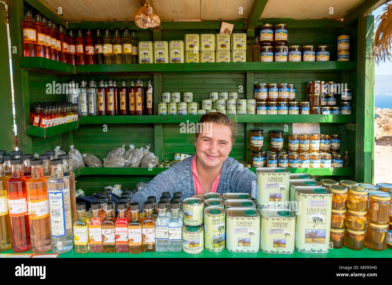 Greek shop assistant offers drinks in her kiosk on the way from the