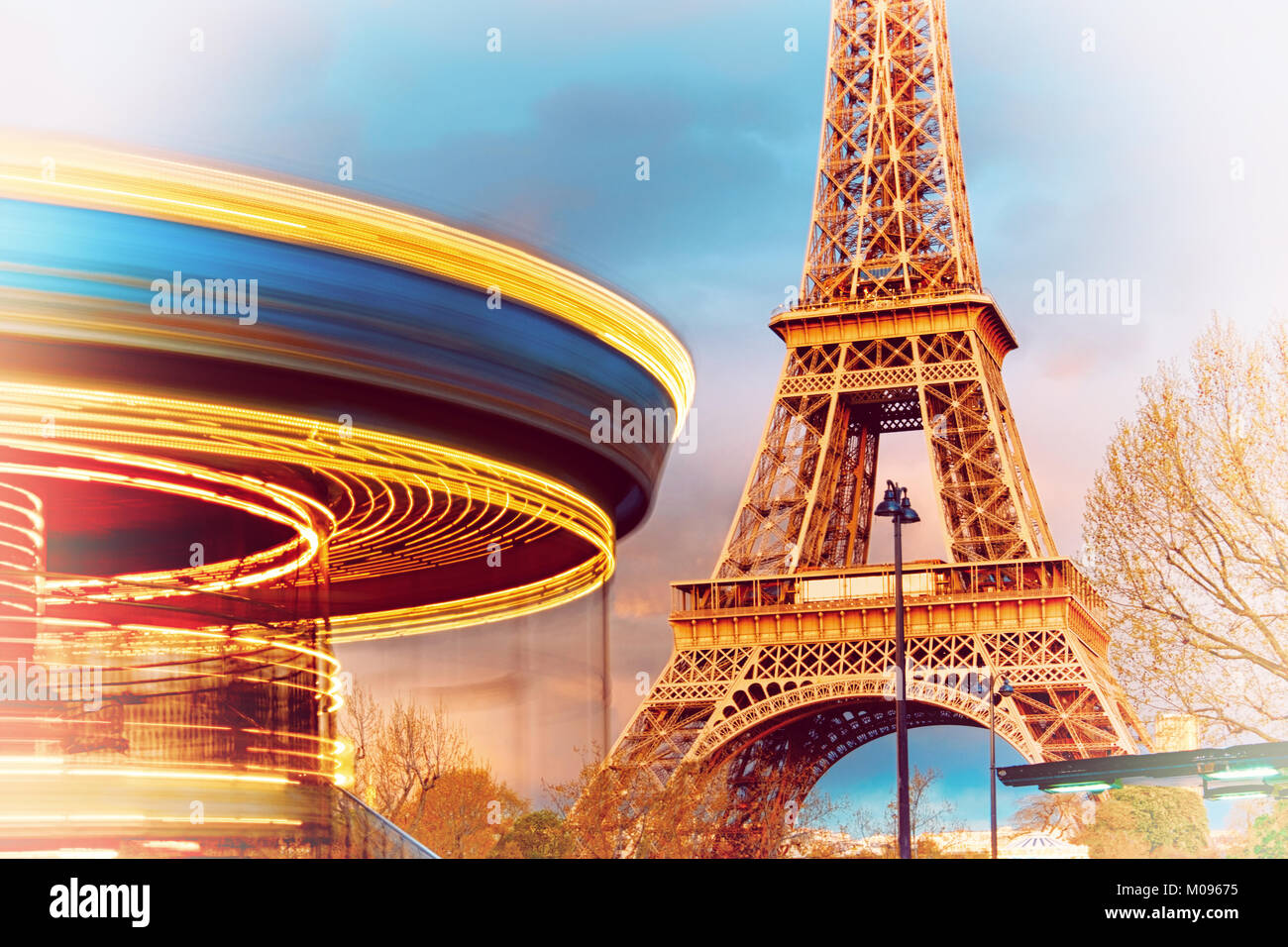 Illuminated vintage carousel rotates  in front of to Eiffel Tower, Paris, on a sunset. The metal tower reflects - Stock Image
