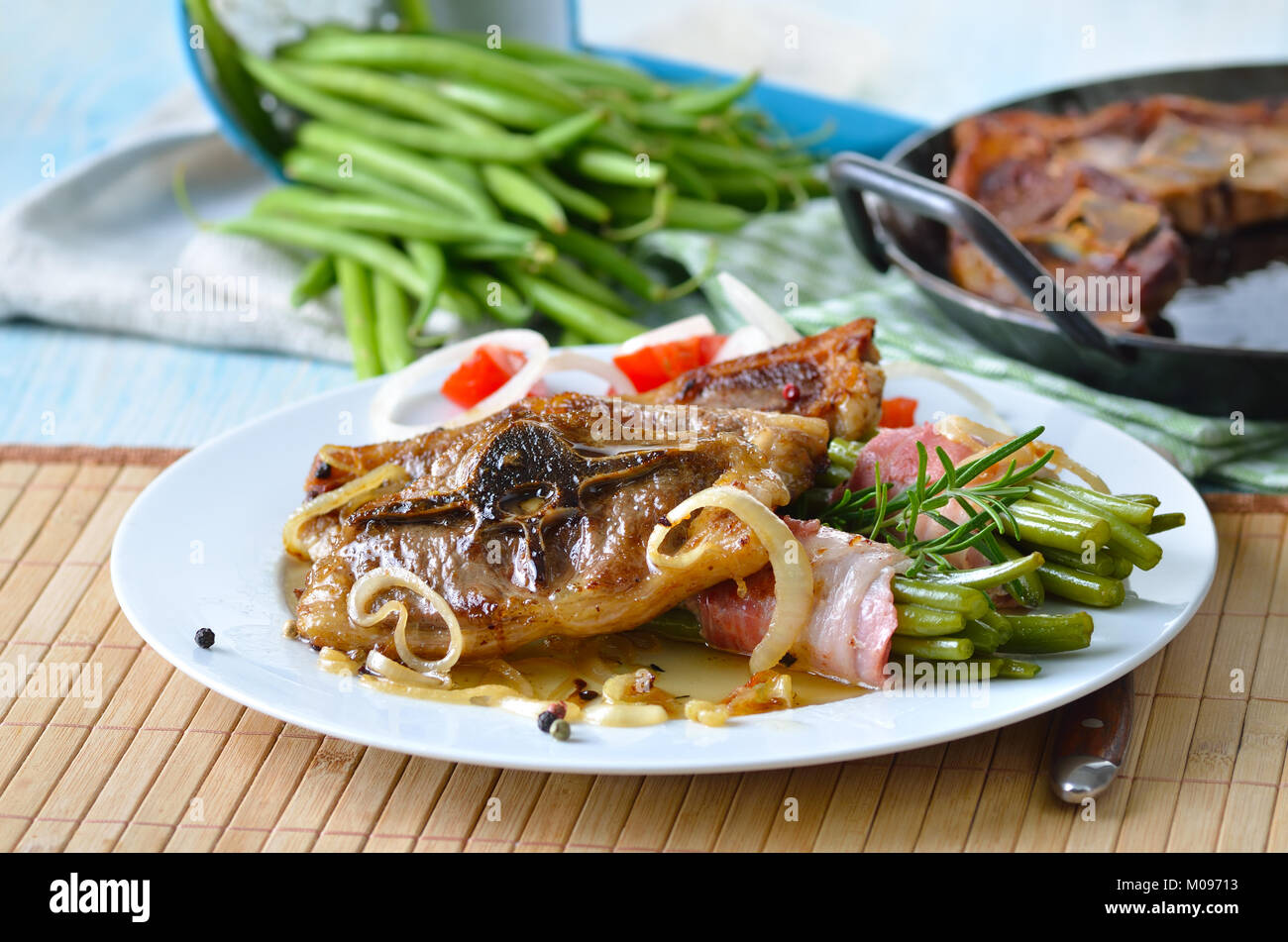 Fried lamb chops with onions and bacon-wrapped green beans Stock Photo
