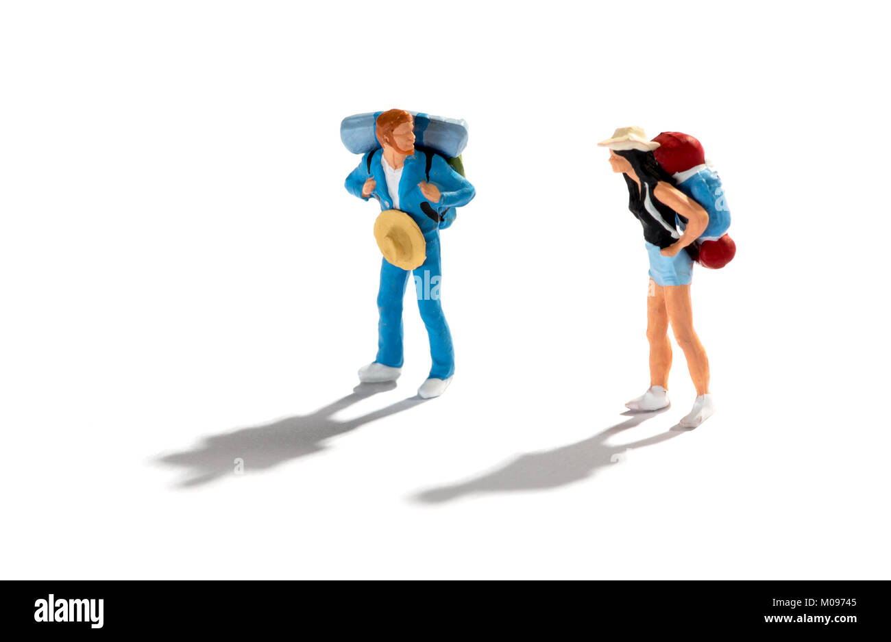 Miniature figures of two travellers or backpackers on a white background with shadows standing looking at each other - Stock Image