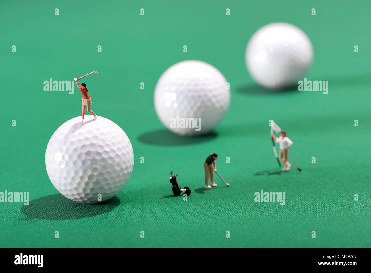Miniature figures of golfers playing a round of golf with one putting for the hole and flag an d the other teeing - Stock Image