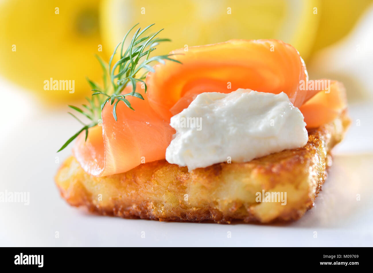 Grated fried potatoes with smoked salmon and creamed horseradish sauce - Stock Image