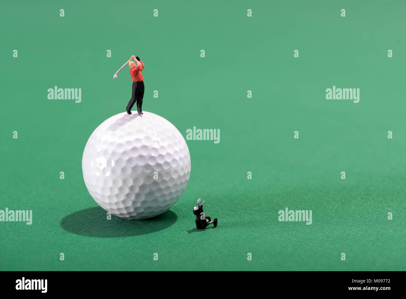 Miniature golfer teeing-off from on top of a ball on a green baize background with copy space - Stock Image