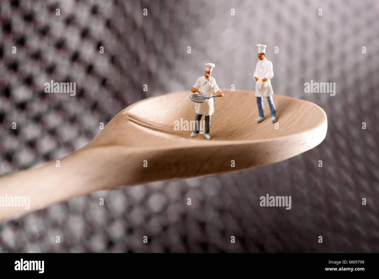 Two miniature figures of chefs or cooks on a wooden spoon over a textured metal background in a concept of catering - Stock Image