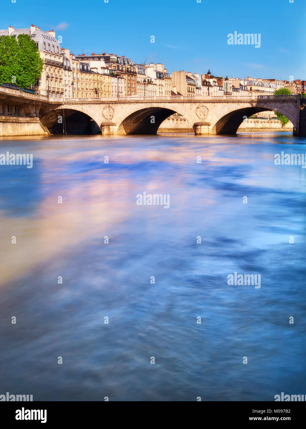 The Pont au Change connecting island Ile de la Cite with the Right Bank. Long exposure to poliish water in Seine - Stock Image