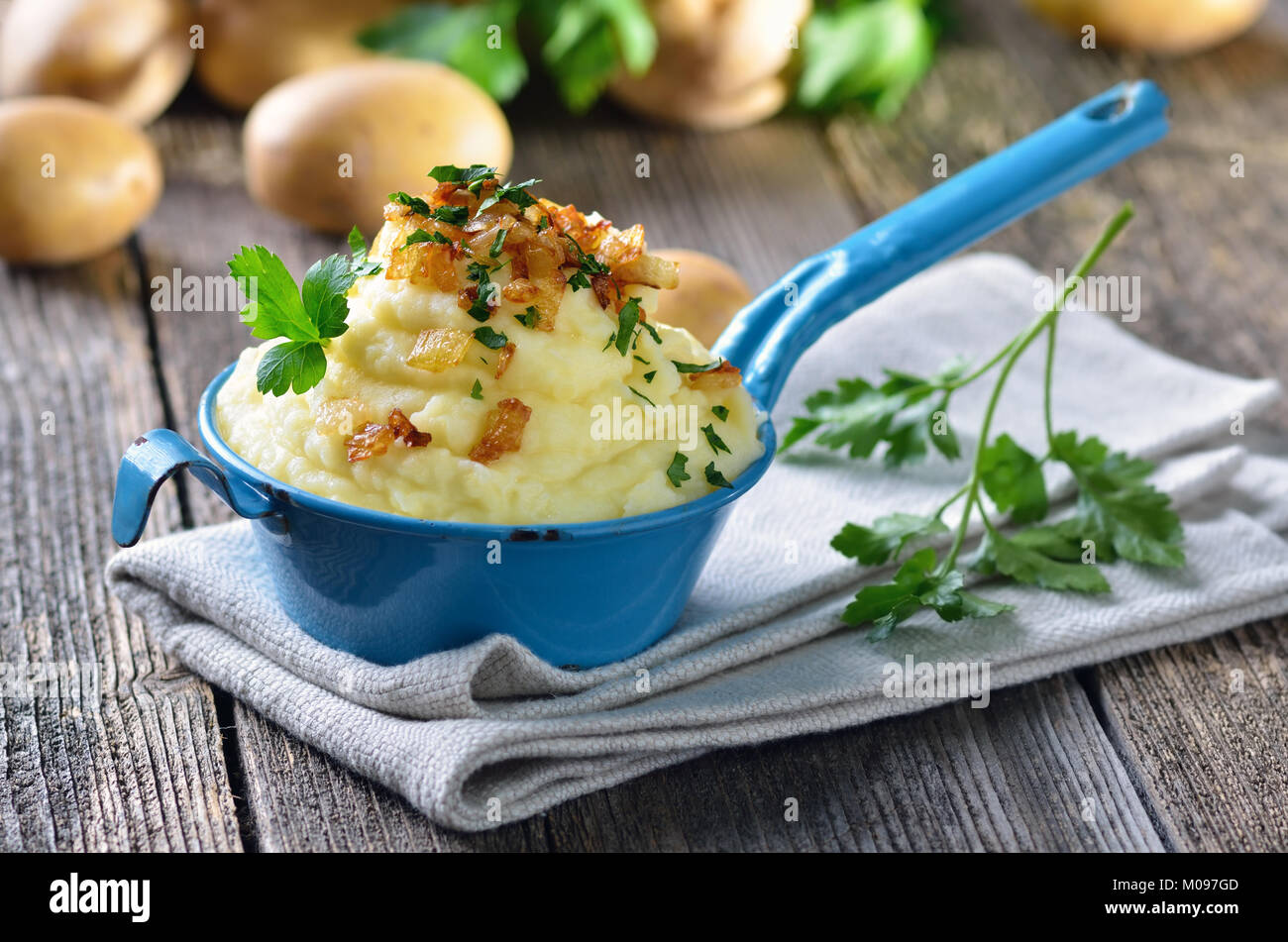 Fresh potato puree with roasted onions in an old enamel coated pot - Stock Image