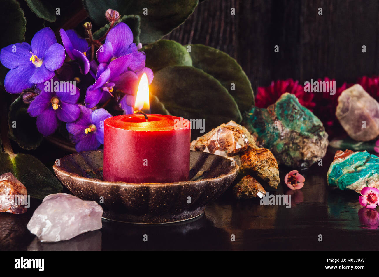 Red Candle with Amethyst, Garnet, Turquoise and Mixed Flowers - Stock Image