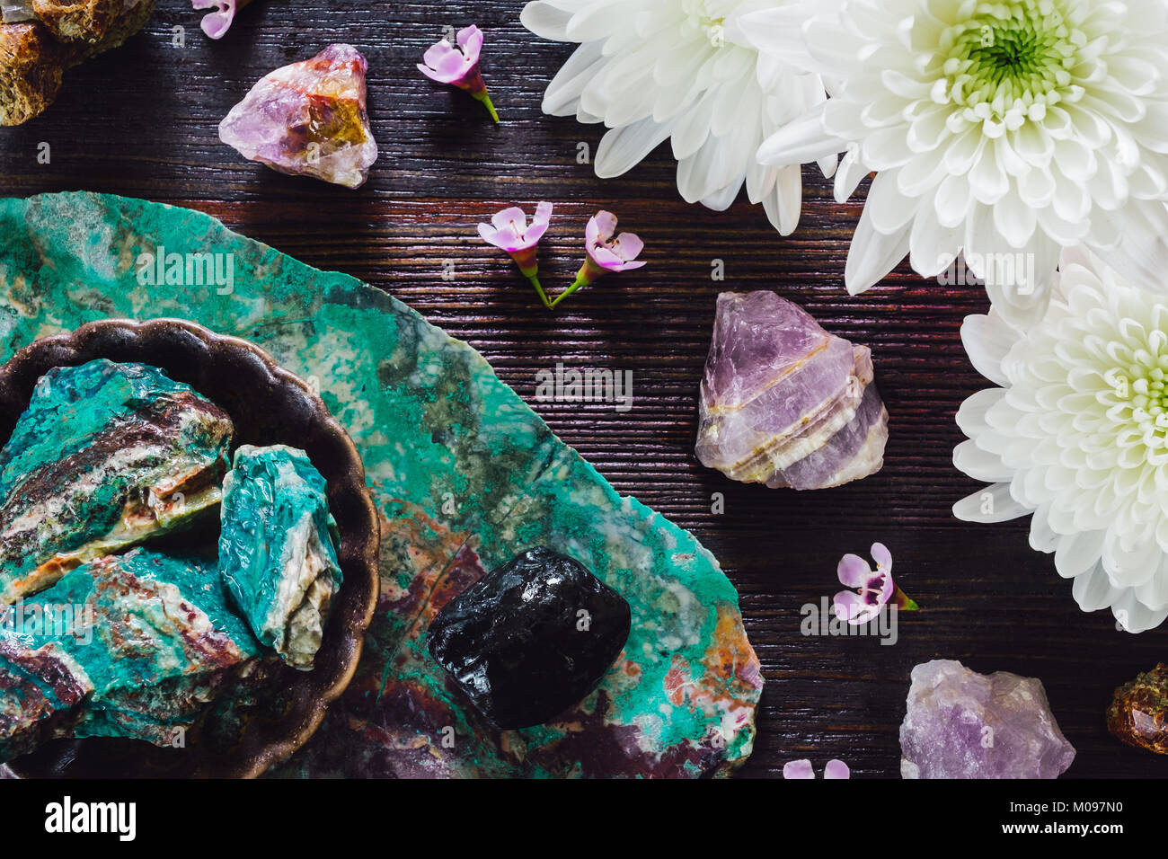 Rough Amethyst, Turquoise, Garnet in Matrix and Onyx with Mixed Flowers on Dark Table - Stock Image
