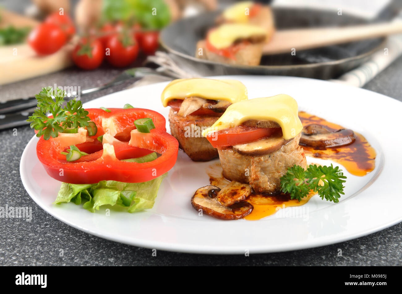 Pork fillets with champignons, tomatoes and melted cheese - Stock Image