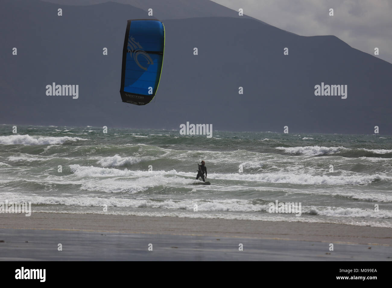 Surfing and playing with a kite on a beach on The Wild Atlantic Way - Stock Image