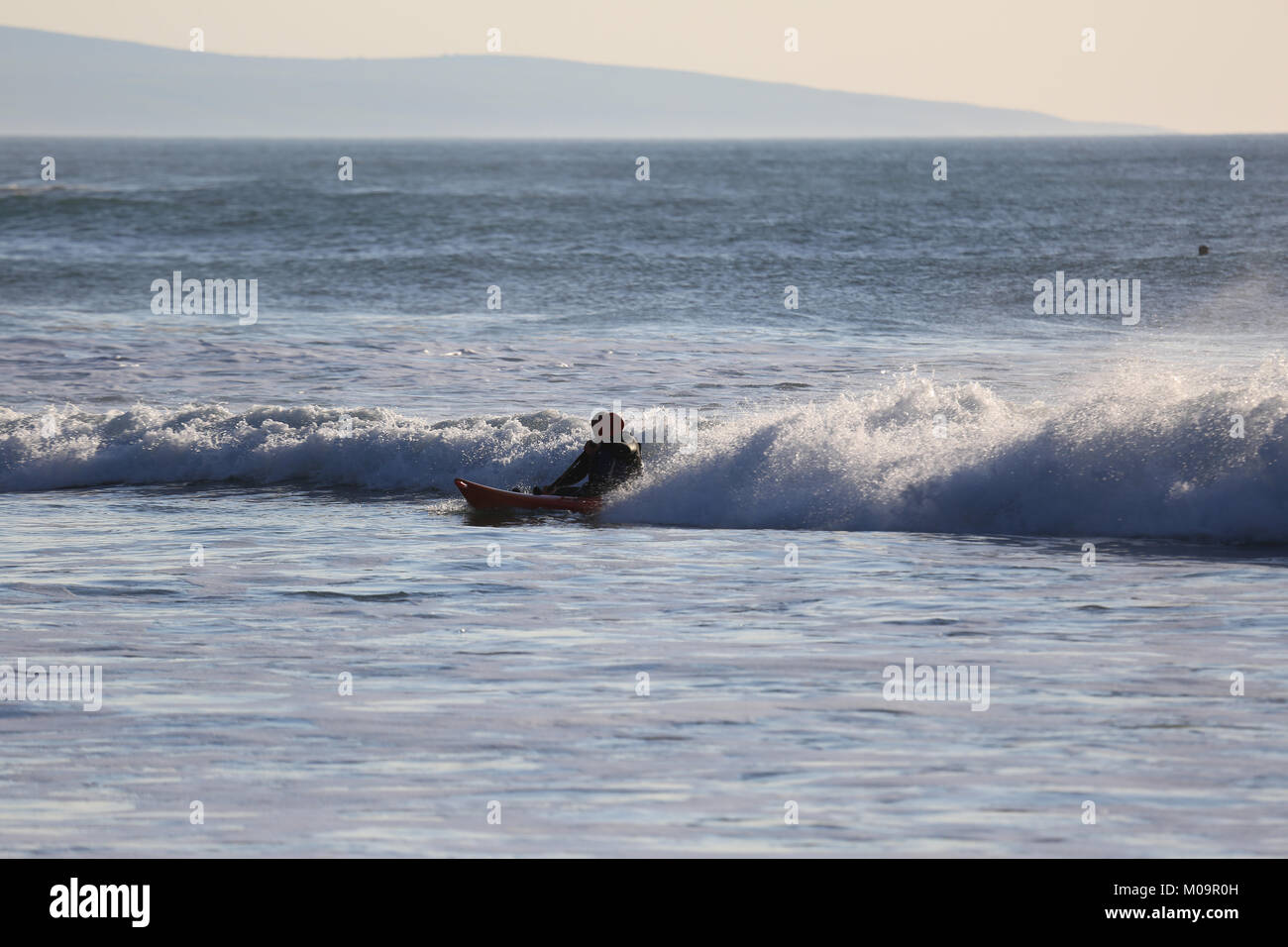 Surfer out surfing on The Wild Atlantic Way - Stock Image