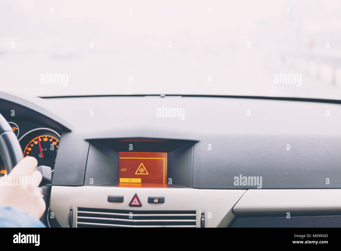 Slippery road warning on car display, car interior point of view - Stock Image