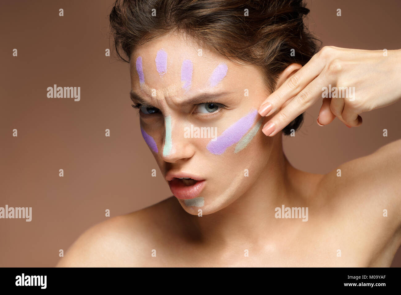 Resolute woman doing makeup using concealer. Photo of beautiful brunette woman on brown background. Skin care concept - Stock Image
