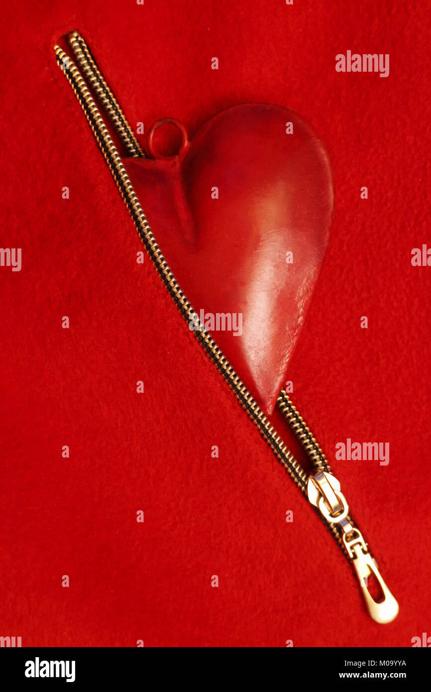 Red heart in red zipper pocket on a red background, wedding or festive concept - Stock Image