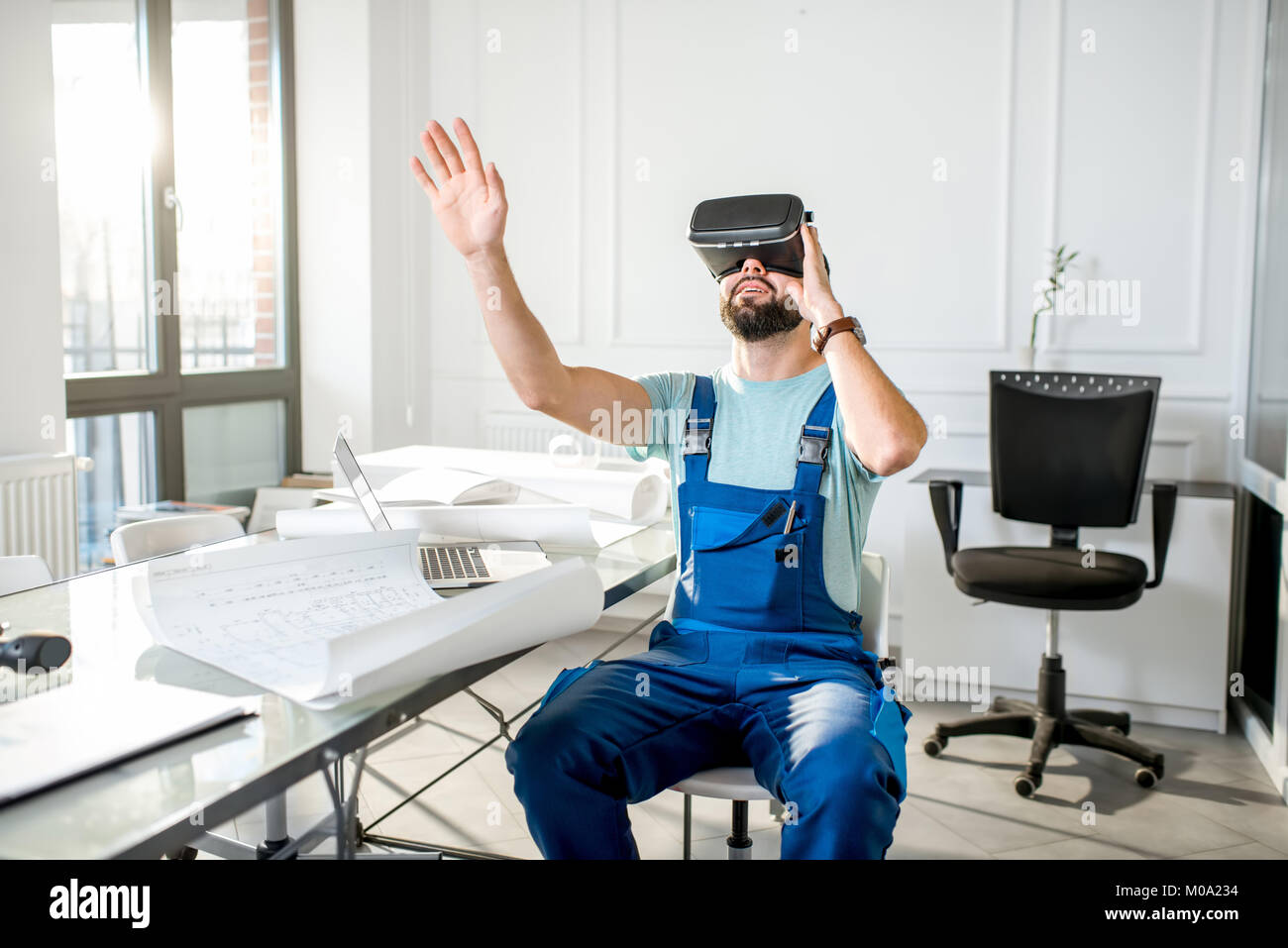 Foreman using vr glasses to imagine projected environment - Stock Image