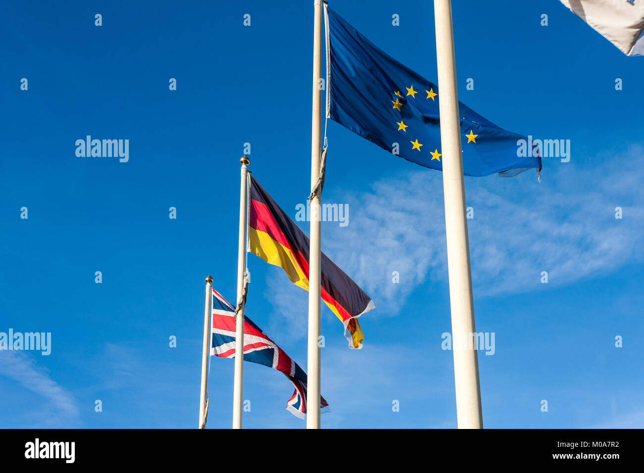 EU Flag, German Flag and UK Flag fly side by side in the breeze - Stock Image