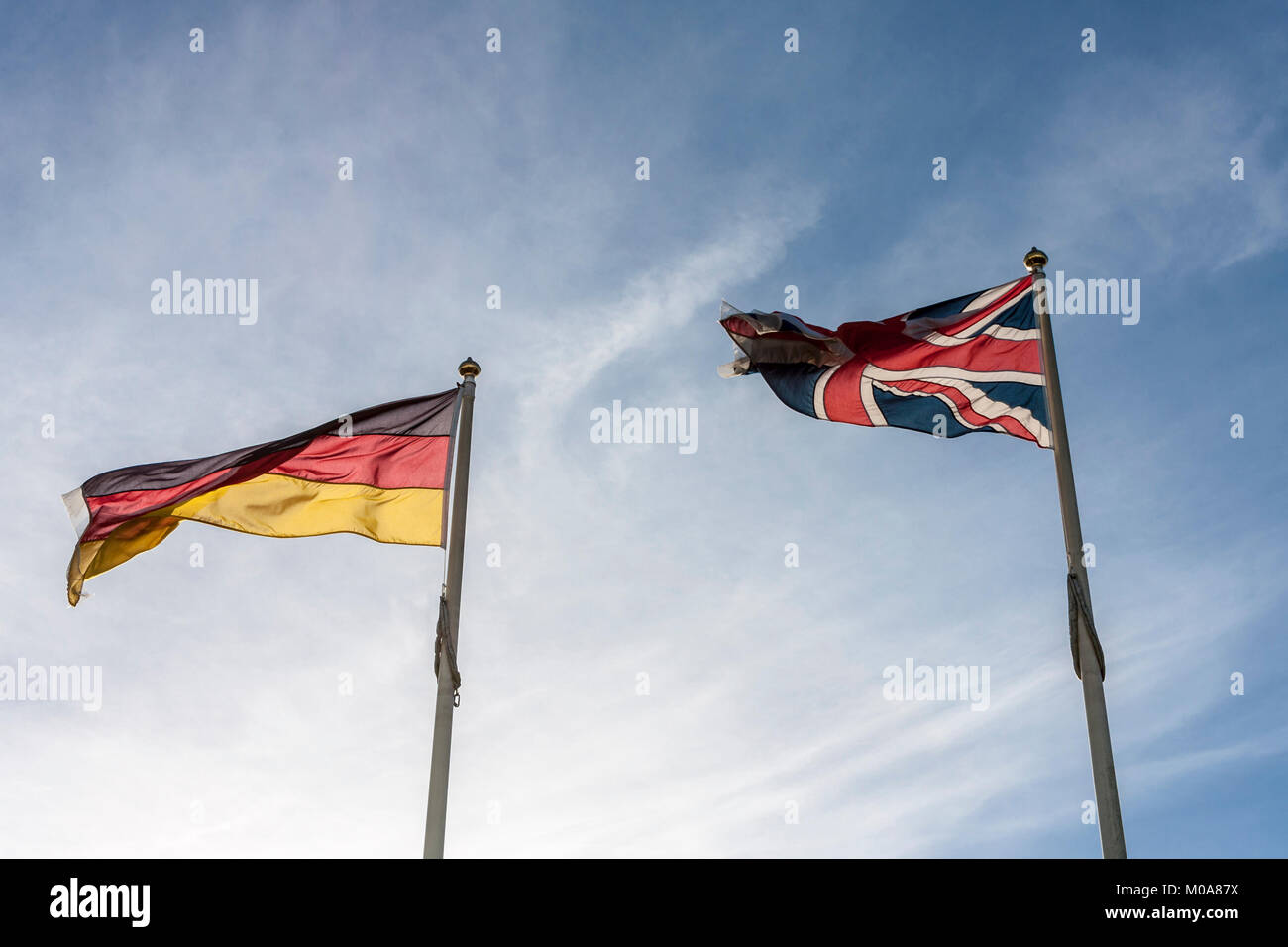 German Flag and UK Flag fly side by side in the breeze - Stock Image