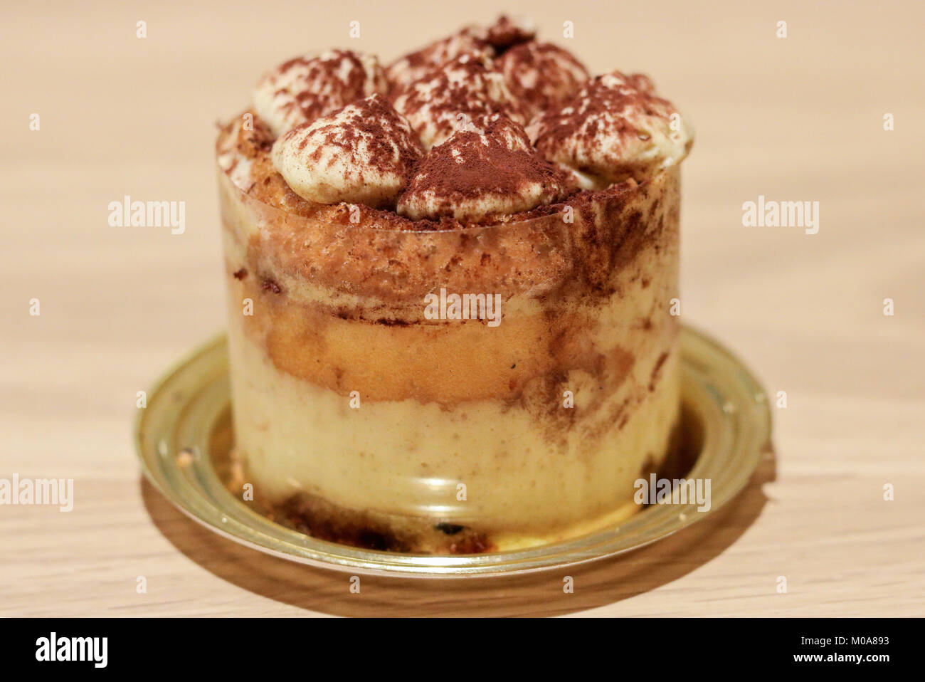 monoportion of italian tiramisù, made with biscuits, mascarpone cheese, coffee and chocolate - Stock Image