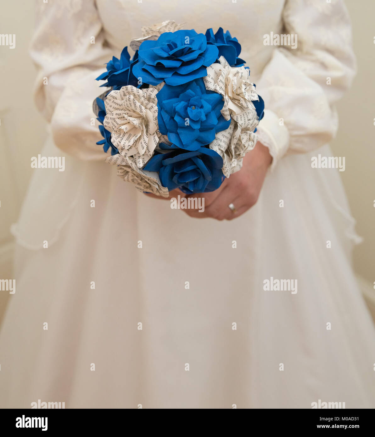 Bride's torso with a home made bouquet of blue and printed paper - Stock Image