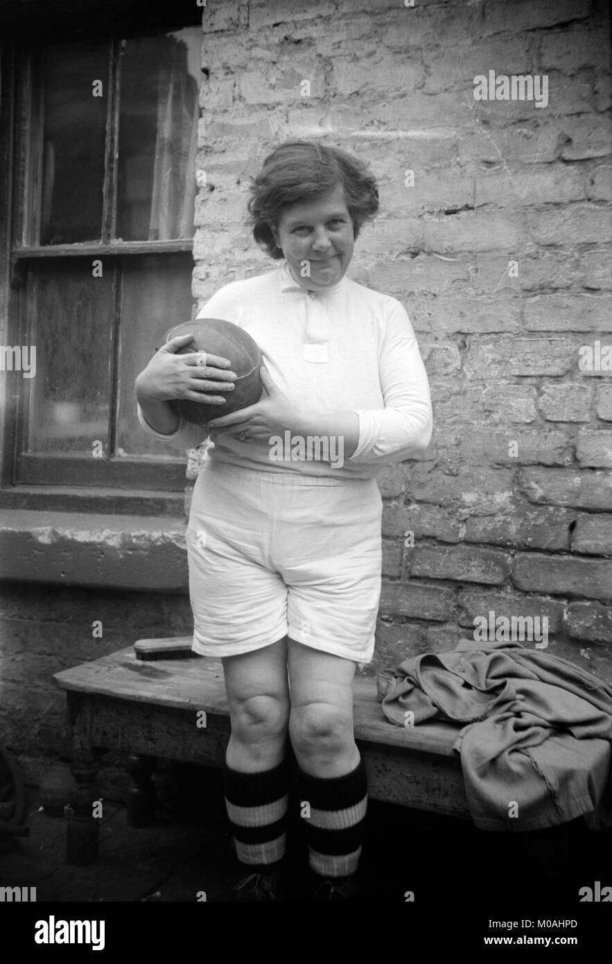 Black and white photo from the early 20th century showing a female dressed in a football (soccer) kit, and holding Stock Photo