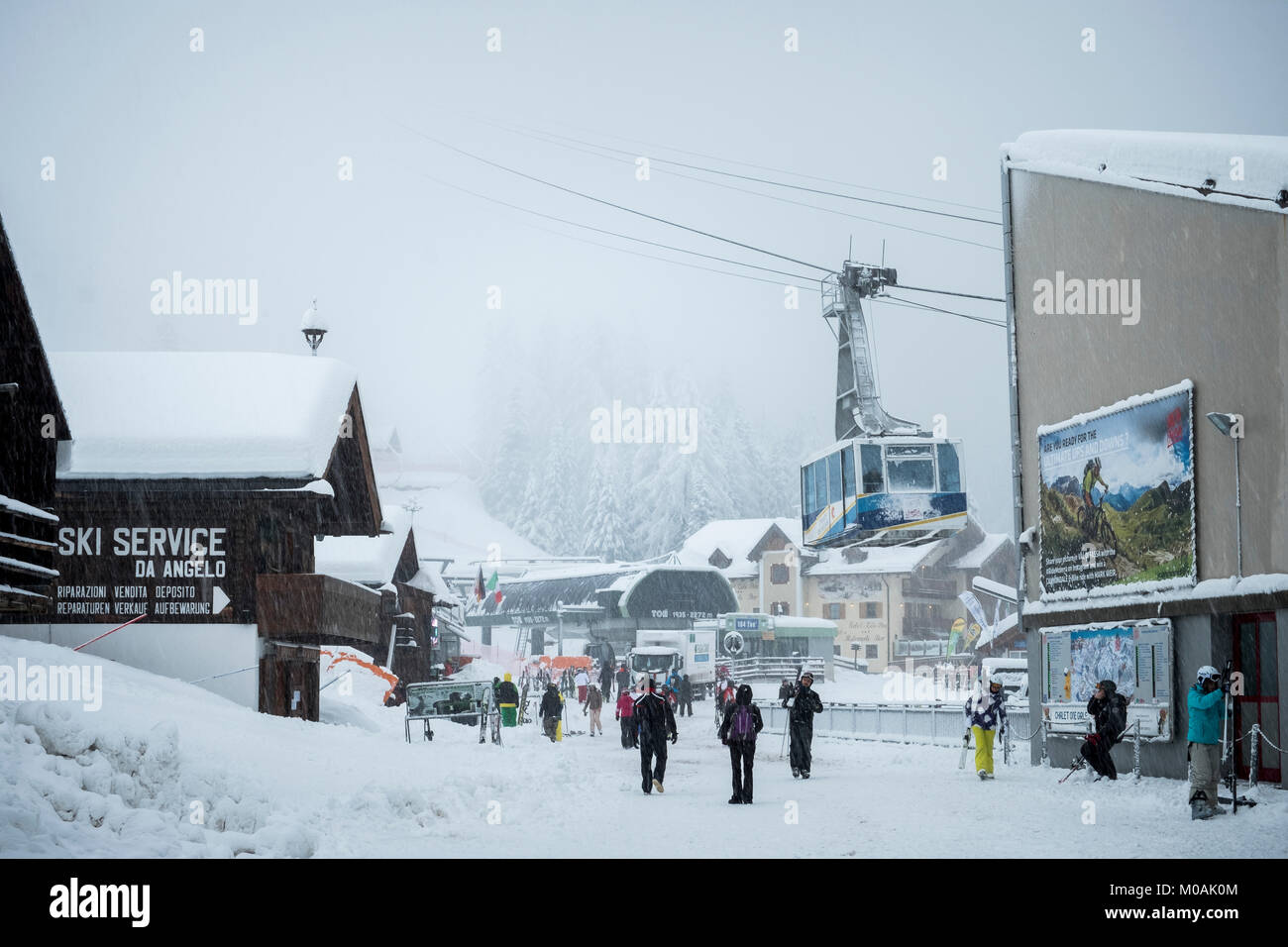 The scene at the top of the cable car above Canezei, at Belvedere, as the snow comes down. A few intrepid skiers - Stock Image