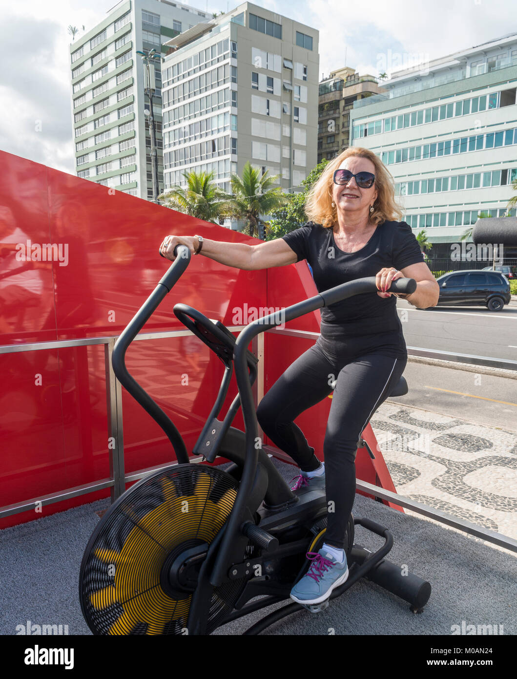 Model Released: Older woman (70-79) exercising on biking machine at open air gym in Rio de Janeiro, Brazil - Stock Image