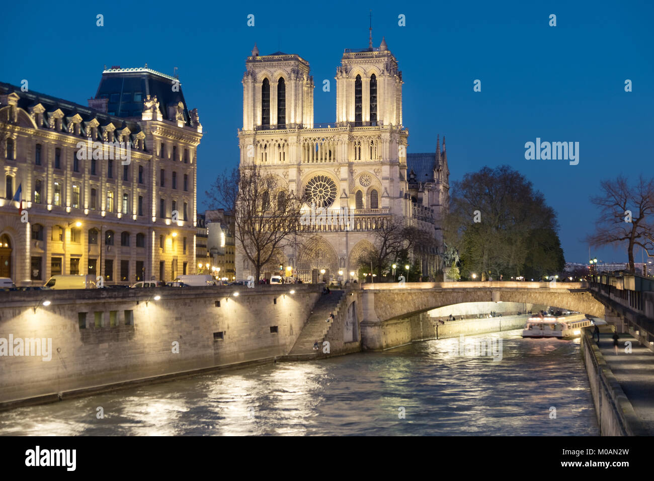 Romantic Paris, illuminated Seine river and Notre-Dame cathedral at night.  Panoramic image, shallow DOF, focus - Stock Image