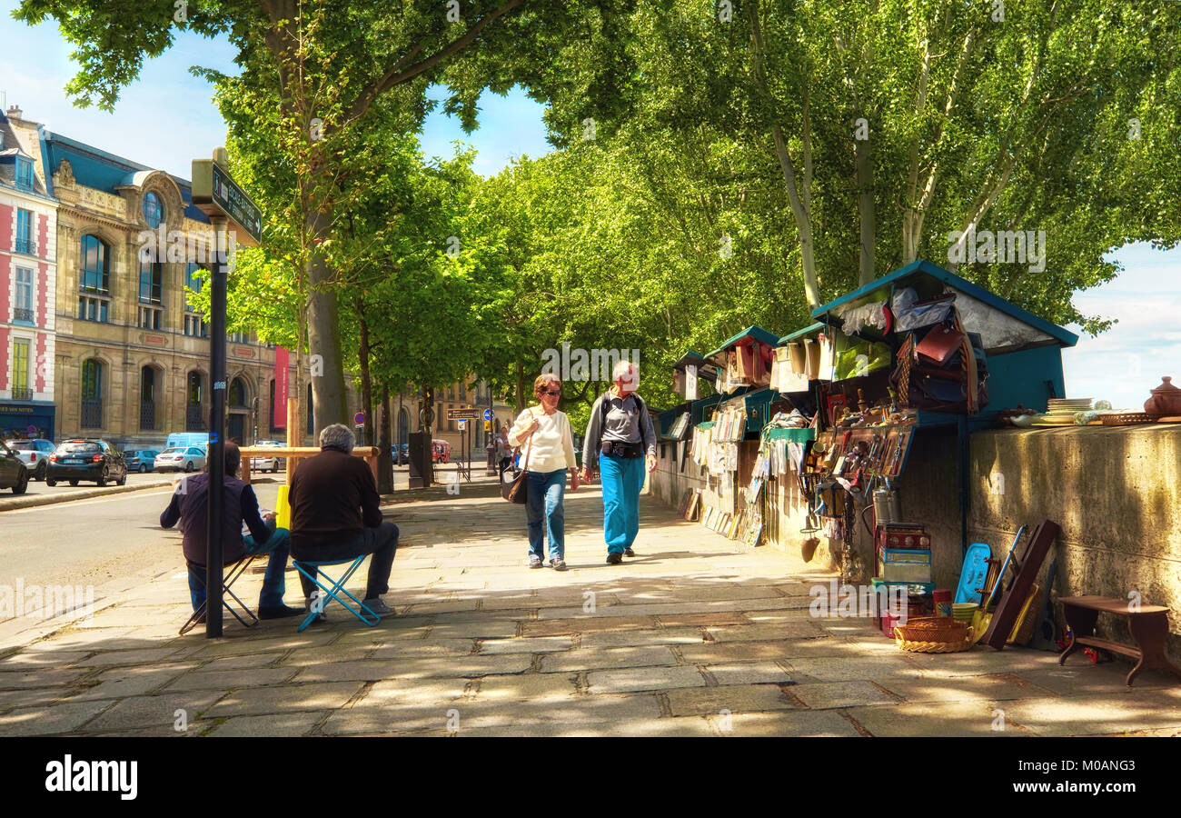 PARIS, FRANCE -  MAY 15, 2017: Tourists walk along river bank passing through second-hand book stalls on a sunny - Stock Image