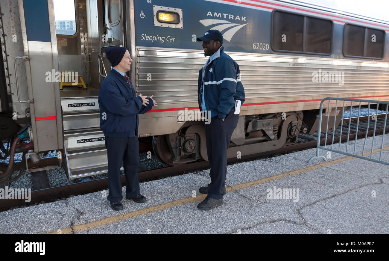 Two male Amtrak porter employees having a conversation while at a station break in Florida. - Stock Image