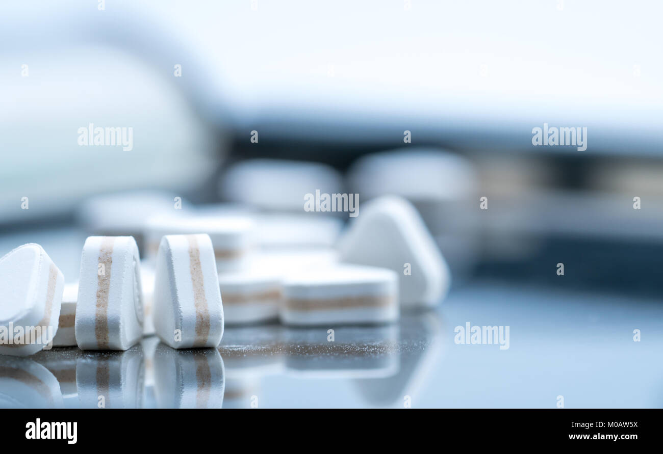 Macro shot of triangle shape tablet pills. Three layers tablet pills for indication antacid, digestive and gastric - Stock Image