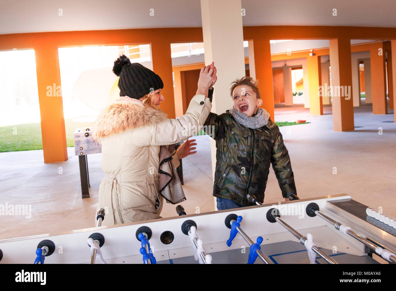 mother and son exulting after victory in the game of table football. concept of people having fun - Stock Image