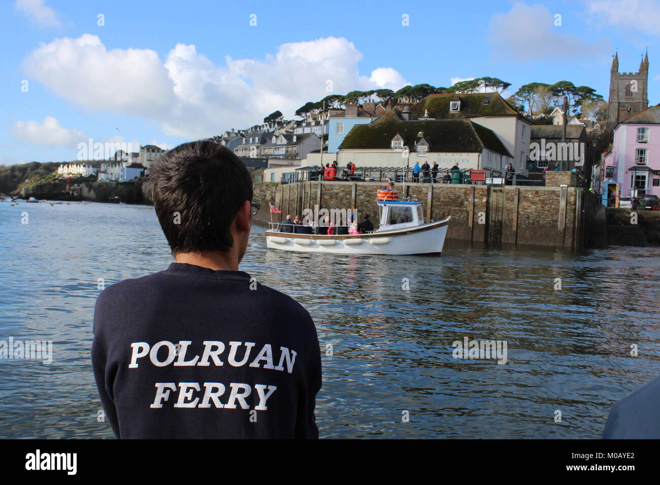 The back of the ferryman wearing a black tshirt with Polruan written on it as the ferry reaches Fowey harbour and Stock Photo