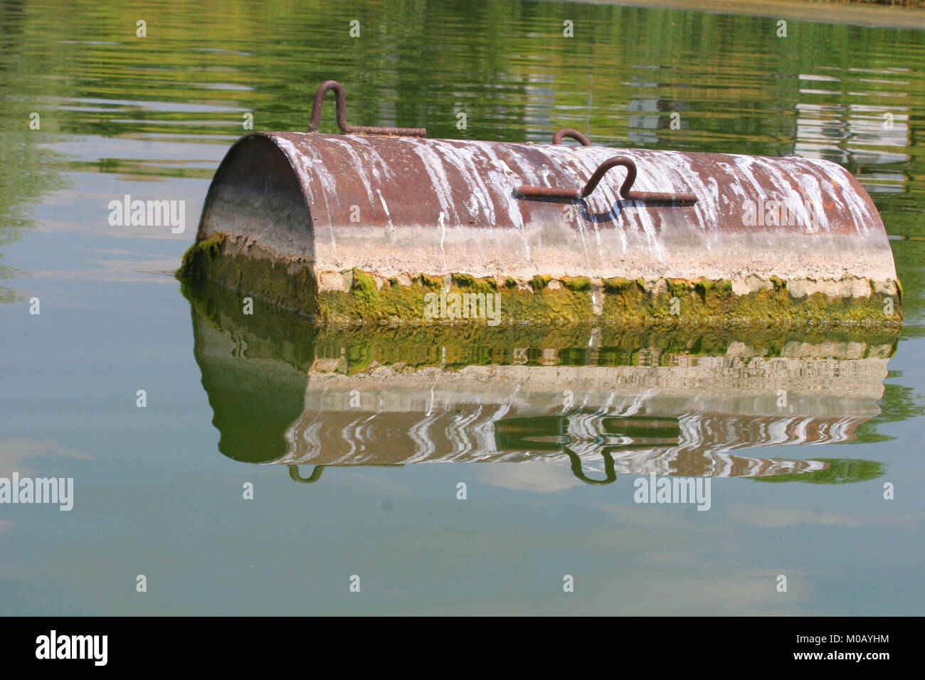 Industrial barrel thrown into the lake for garbage and make a big pollution. Water pollution. Climate changes. Industry - Stock Image