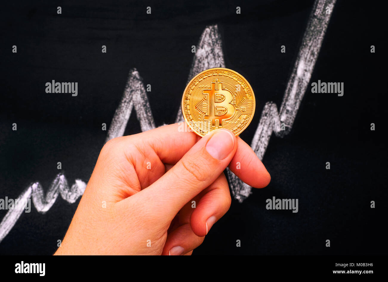 Woman hand holding golden Bitcoin virtual coin against blackboard with chalk drawing graph. - Stock Image