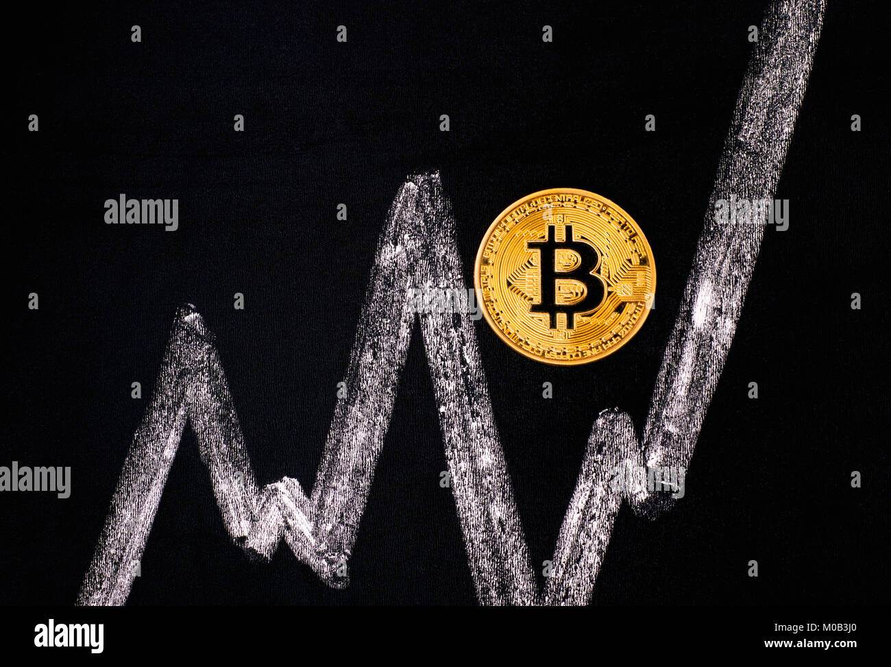 Golden Bitcoin virtual coin on blackboard with chalk drawing graph. - Stock Image